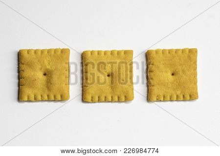 Cheese Flavored Small Square Crackers On A White Background