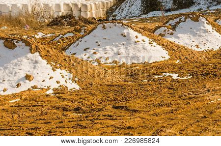 Rural Winter Landscape Of Three Dirt Mounds Partially Covered With Snow With Rolled Hay Bails Wrappe