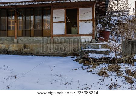 Old Abandoned Wooden House With Sliding Doors And Concrete Porch And Snow Covered Lawn In A Rural Ar