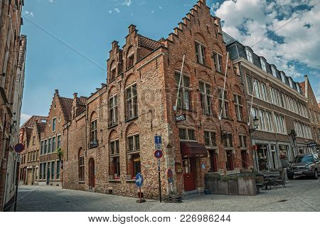 Bruges, Belgium - July 05, 2017. Brick Buildings In Empty Street And Blue Sky At Bruges. With Many C
