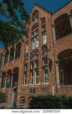 Brick Facade Of Building And Doctor Thomas Montanus Bust At City Center Of Bruges. With Many Canals