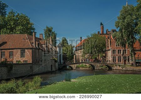 Old Brick Buildings Next To The Canal And Bridge With People In A Sunny Day At Bruges. With Many Can
