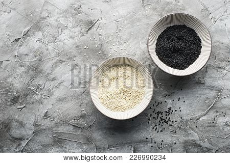 White And Black Sesame In The Same Ceramic Bowls On A Gray Background. Top View. Copy Space