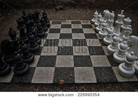 Street Chessboard With Black And White Chessmen In The Park
