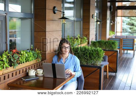 Female Online Shop Consultant Speaking By Smartphone At Cafe And Using Laptop. Young Woman Dressed I