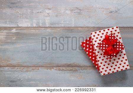 Gift Boxes Wrapped In Polkadots And Hearts Paper With Ribbon On Blue Wooden Background, Vintage Retr