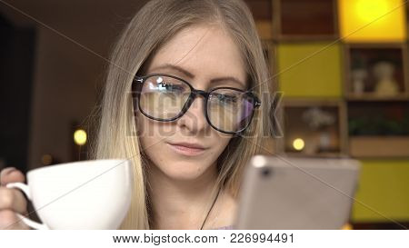 Coffee Break. Young Female Using Smartphone While Drinking Coffee