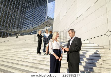Political Scientists With Tablet And Document Cases Going Down Stairs And Talking. Concept Of Offici