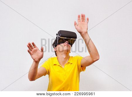 Young Man In Virtual Reality Glasses By The Wall