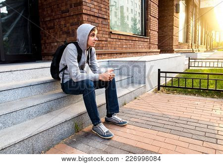 Young Man Sit On The Porch At The City Street
