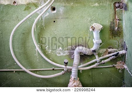 Water And Sewer Pipes On The Background Of The Old Wall. Repair In The House. Connection Of Metal-pl