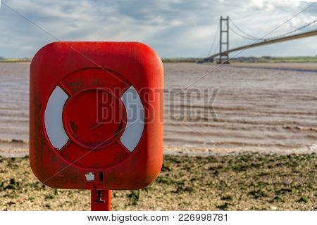 A Lifebelt On The Shore Of The River Humber, With The Humber Bridge In The Background, East Riding O