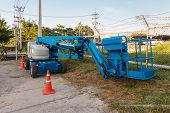 Blue articulated boom lift for construction work poster