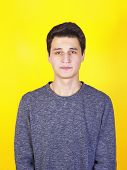 Confused young man looking at camera shyness, shame or humiliation isolated on a yellow background. poster