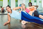Beautiful fit woman smiling while wearing blue fitness sleeveless top and leggings during group workout class of foam rolling at the gym poster