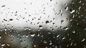 Raindrops On A Old Window With Contrast By Light Sky And Dark Vegetation