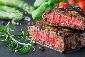 Medium Roasted Steak With Asparagus And Tomatoes On Slate Plate