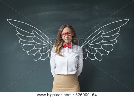 Young Smiling Woman Teacher Or Student Angel With Chalk Wings On Blackboard