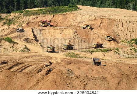 A Lot Of Mining Trucks Work In An Sand Open Pit .dump Truck Transporting Stone And Gravel . Mining Q