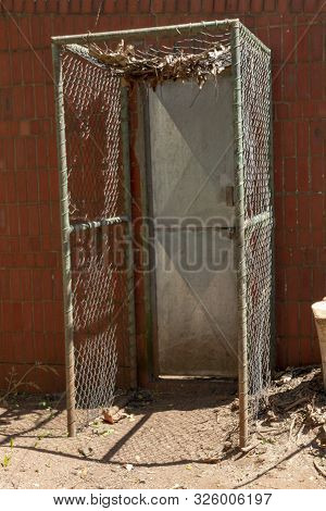 A Close Up View Of A Metal Door Leading Into An Enclosed Area