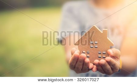 Small Home Model On Woman Hand. Family Life And Business Real Estate Concept. Vintage Tone Filter Ef