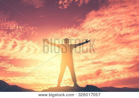 Copy Space Of Man Hand Raising On Top Of Mountain And Sunset Sky Abstract Background. Freedom Travel