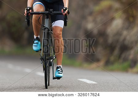 Female Cyclist Riding Racing Bicycle, Woman Cycling On Countryside Summer Road. Training For Triathl