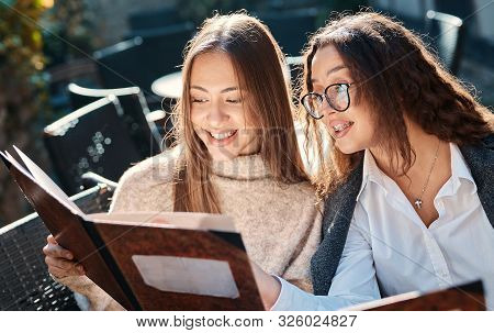 Two Cheerful Young Smiling Women Having Lunch In Street Cafe And Looking At Menu