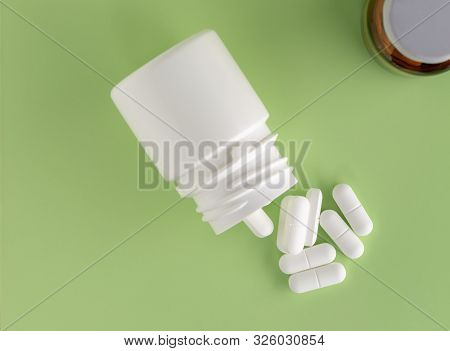 Various Plastic And Glass Medicine Bottles And White Pills Around On A Colored Background