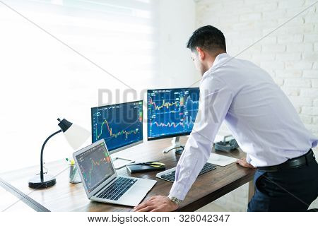 Hispanic Young Male Stock Trader Standing While Analyzing Graph From Computer Screen At Home