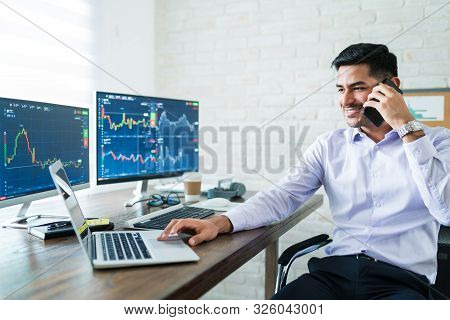 Smiling Young Male Online Stock Trader Talking On Smartphone With Client While Using Laptop At Desk
