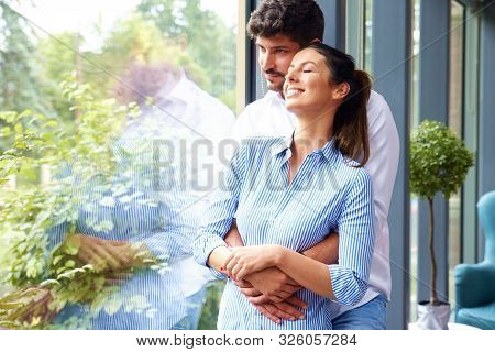 Beautiful Young Couple Standing At The Window And Relaxing