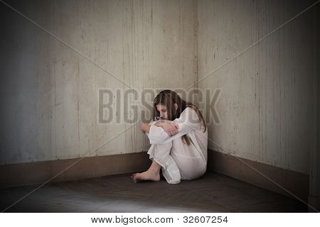 Lonely mad woman sitting in the corner of a room