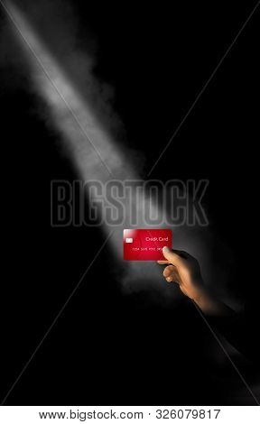 A Hand Holds A Credit Card In A Shaft Of Light With A Little Fog. The Theme Is Focusing On Credit Ca
