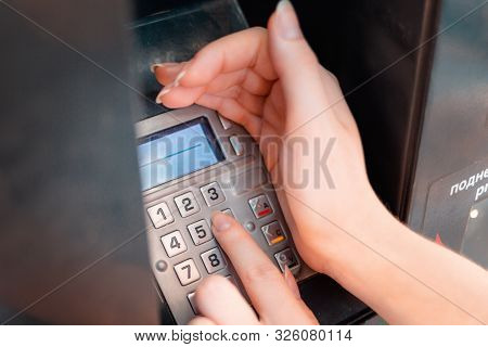 Atm And Banking Operations. The Woman Covered With His Hand, Drives A Pin From A Bank Card In The Ma