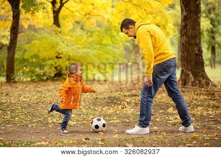 Father And Little Toddler Son Having Fun In Autumn Park: Dad And Child Playing Football Outdoors, Ki