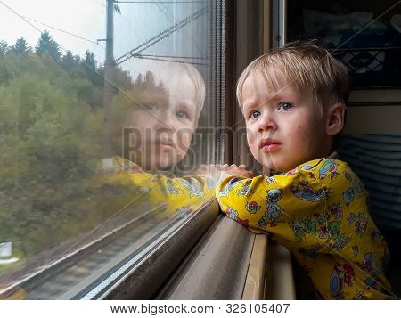 A Bright, Cute Three-year-old Boy Riding A Train Looks Out The Window, Behind Which A Dull Landscape