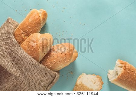Three French Mini Baguettes With Sesame In Sackcloth Bag And Torn Baguette Isolated On Blue Backgrou