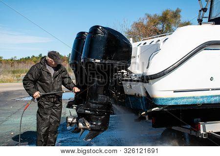 Caucasian Man Pressure Washing Outboard Motors On Power Boat