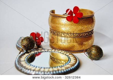 Indian bracelet with a picture of the sun, round mirror and red earrings