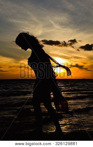 Feminine Silhouette On The Red Sunset Background