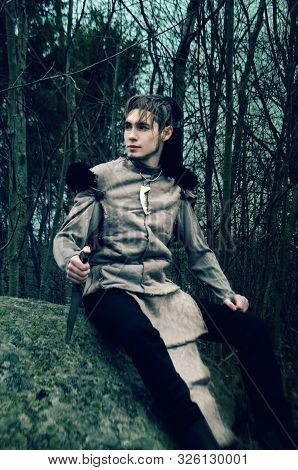 Young Man In The Costume Of A Barbarian Sitting On A Stone In The Dark Forest