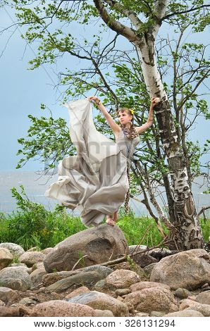 Woman In A Gray Silk Dress, Fanned By The Wind Is About The Birch On A Rocky Beach