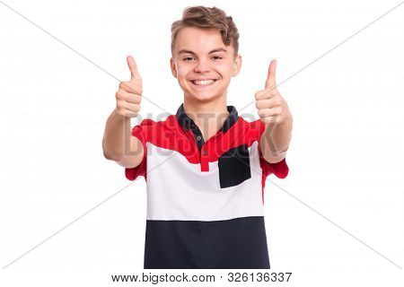 Portrait of teen boy making thumbs up gesture, isolated on white background. Handsome caucasian young teenager smiling and showing success sign. Happy cute child looking at camera.