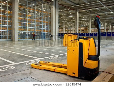 Electric forklift in large modern storehouse