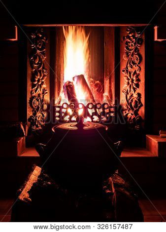 An Old Cauldron Standing In The Dark In Front Of The Wood Burning In The Fireplace. Mystical Fairy T