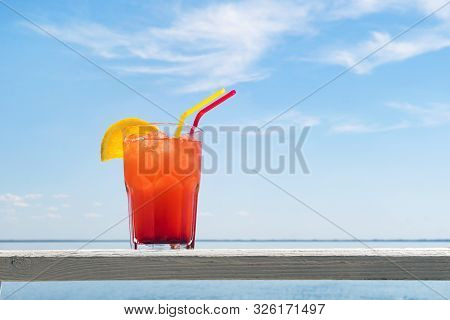 Bocal Of Fruity Cocktail On A Beach Table. Glass Of Red Berry Juice With A Straw And A Slice Of Oran