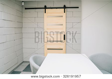 poster of Sliding Barn Door on Foam Brick Wall and Furniture Element of Meeting Room Conceptual Cozy Interior Copyspace. Table and Stylish Armchair on Grey Carpet. Conference Corporate Business Workplace