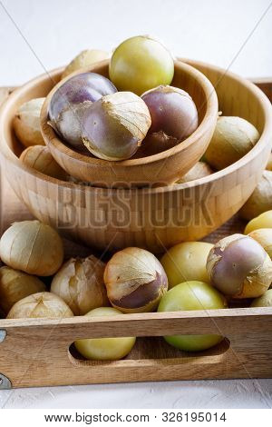 Ripe Tomatillo (mexican Husk Tomato, Physalis Philadelphica, Vegetable Physalis) In Wooden Tray On W