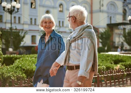 I Love My Husband. Happy And Beautiful Elderly Couple Holding Hands And Looking At Each Other While
